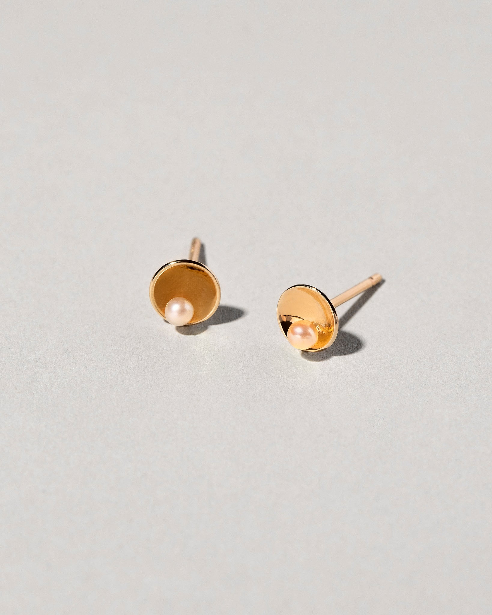 Front and three quarter view of Pearl Cup Stud Earrings
