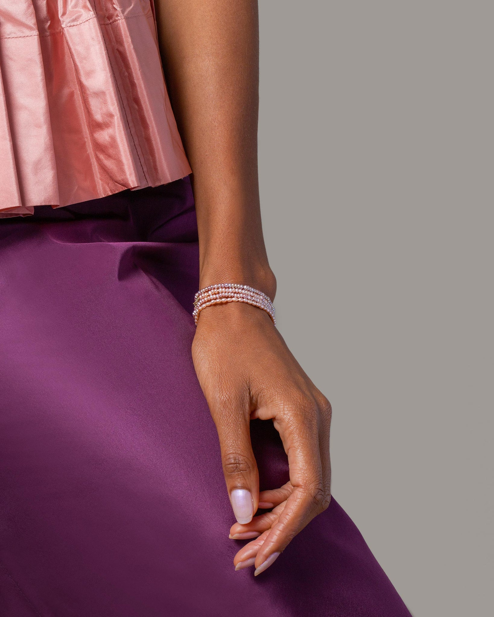 Pink and Lavender seed pearl bracelets worn on model