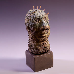 Concrete sculpture of head with nails