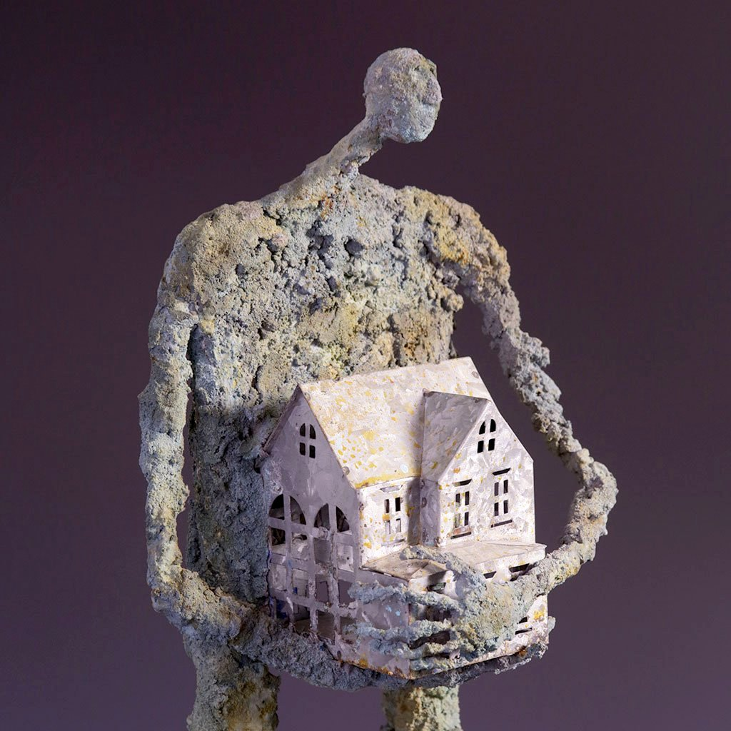 Concrete figure holding small metal house
