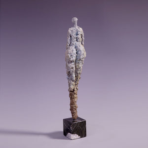 Female figure sculpture on marble base, back view