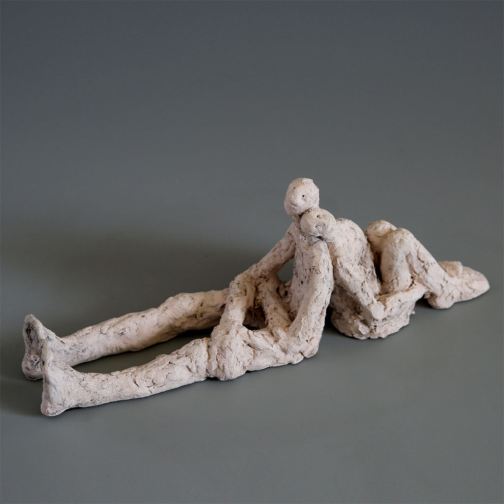Ceramic couple sitting back to back