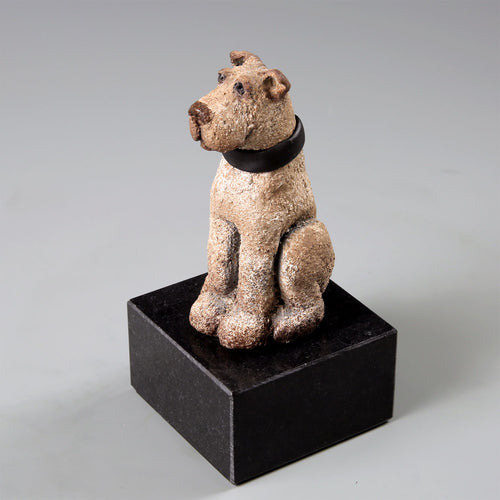 Small ceramic mutt dog on black marble base