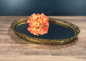 gold rimmed vanity mirror with a flower
