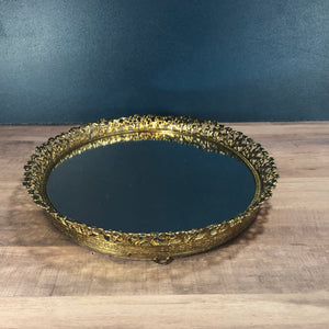 gold rimmed vanity mirror sitting on a table