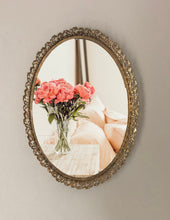 gold mirror frame hanging on a wall