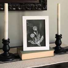 framed photo of dandelions with two candlesticks