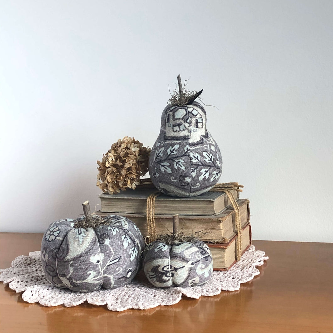 gray floral fabric pumpkins and pear on a stack of books