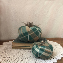 Two plaid fabric pumpkins on a stack of books