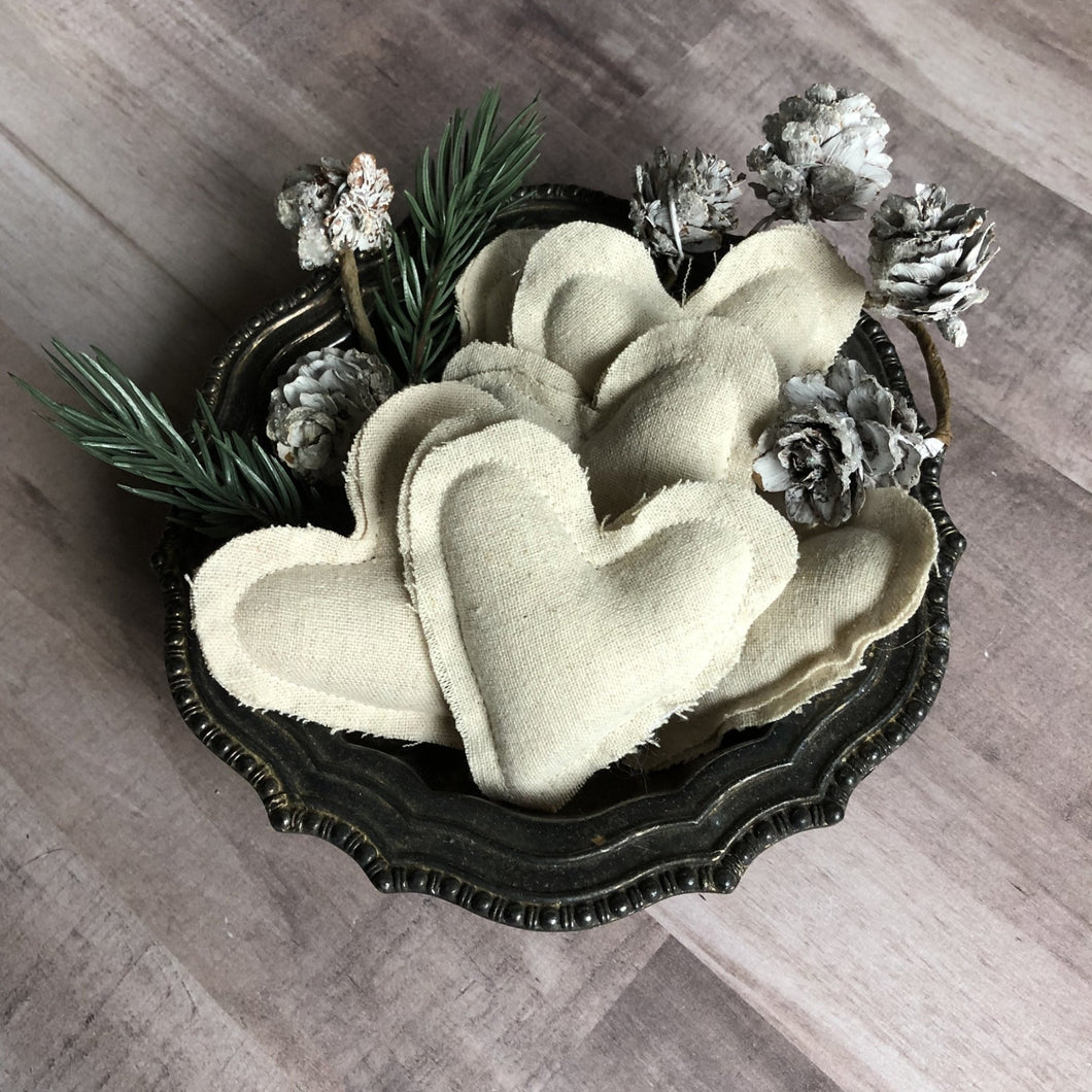 cream fabric hearts in a shallow bowl