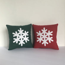 green and red pillow with snowflake