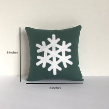 green pillow with cream snowflake