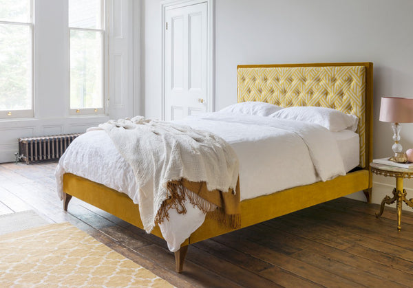 Bedroom with a modern bed in a yellow fabric
