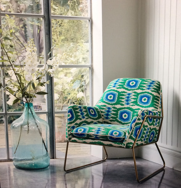 Living room with a contemporary chair in a printed velvet fabric