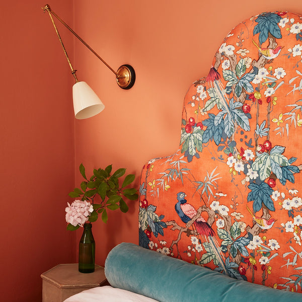 Bedroom with vibrant orange floral headboard