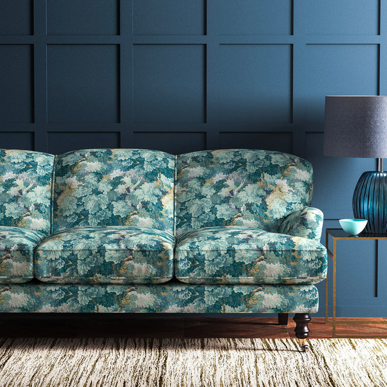 Sofa upholstered in a teal velvet upholstery fabric with blue tree design and stain resistant finish