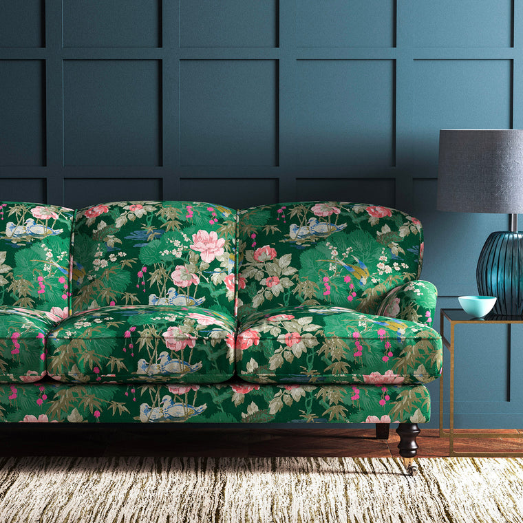 Sofa upholstered in a green and pink velvet upholstery fabric with floral and bird design with a stain resistant finish