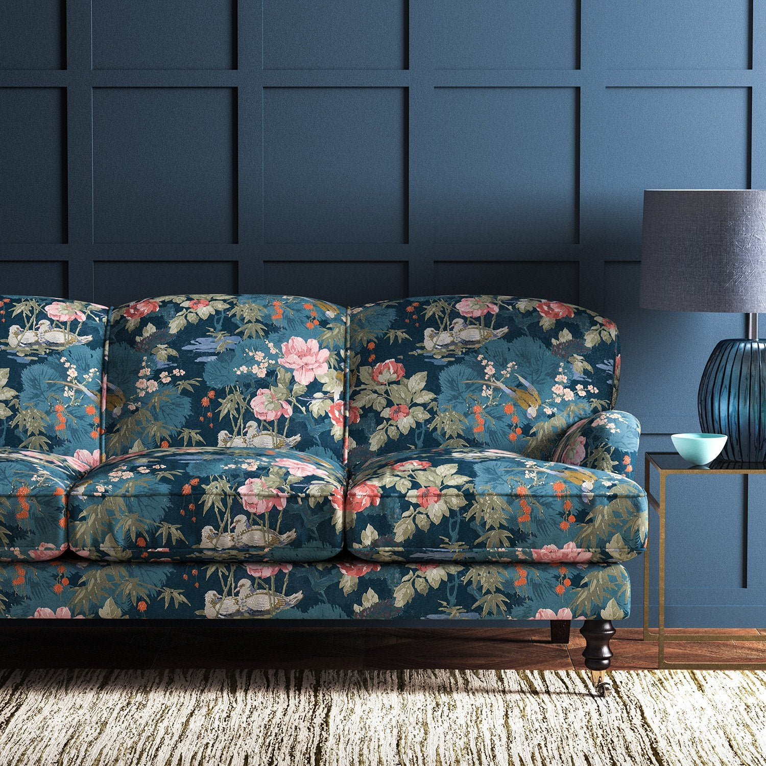 Velvet sofa upholstered in a blue velvet upholstery fabric with floral and bird design with a stain resistant finish