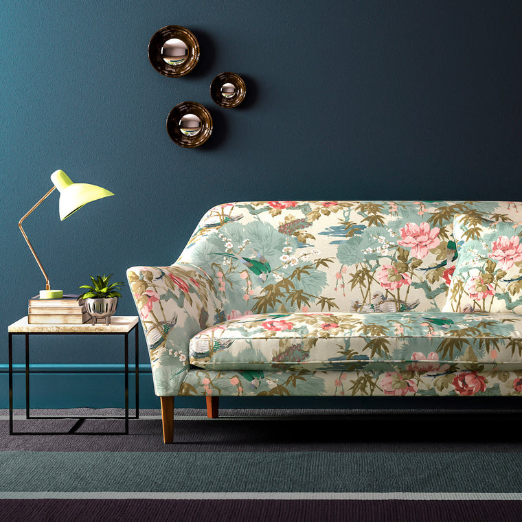 Velvet sofa upholstered in a light blue and pastel velvet upholstery fabric with floral and bird design with a stain resistant finish