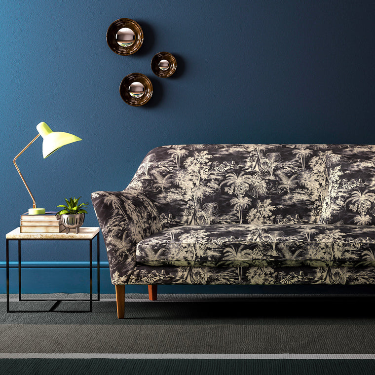 Sofa upholstered in a grey and white velvet upholstery fabric with palm tree design and stain resistant finish