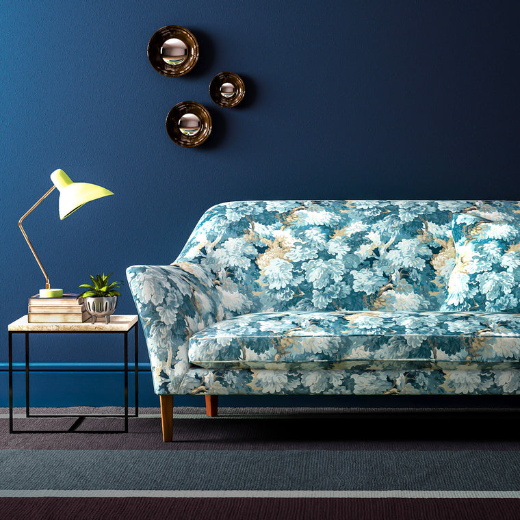Sofa upholstered in a blue velvet upholstery fabric with blue tree design and stain resistant finish