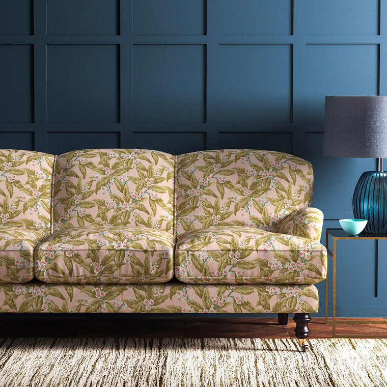 Velvet sofa upholstered in a peach and ochre leaf and blossom velvet upholstery fabric with a stain resistant finish