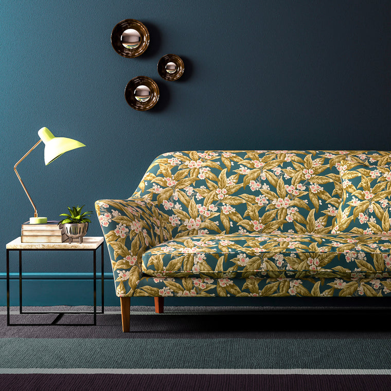 Sofa upholstered in a blue and ochre leaf and blossom velvet upholstery fabric with a stain resistant finish