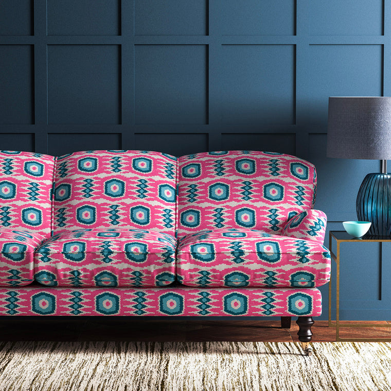 Sofa upholstered in a pink and blue velvet upholstery fabric with abstract print and stain resistant finish