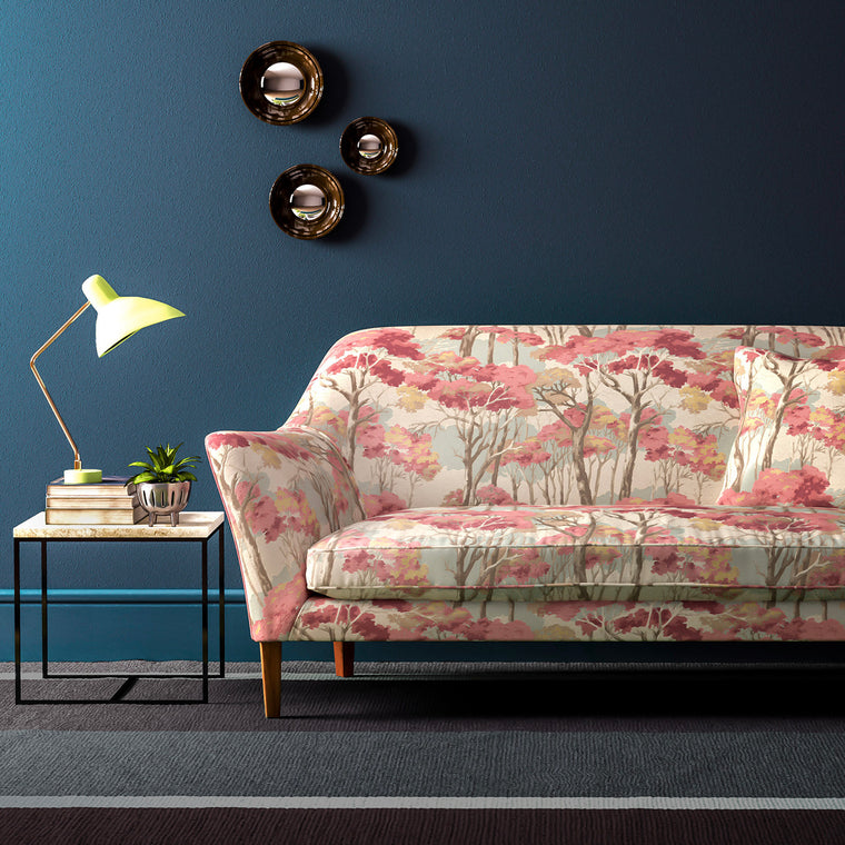 Velvet sofa upholstered in a velvet upholstery fabric with stain resistant finish and pink and light neutral tree design