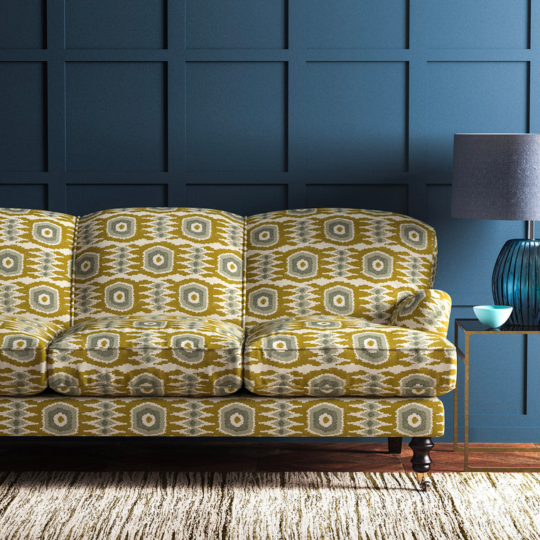 Velvet sofa upholstered in a ochre velvet upholstery fabric with abstract print and stain resistant finish