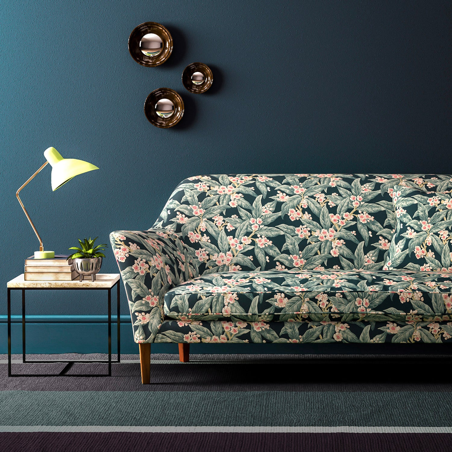 Sofa upholstered in a blue leaf and blossom velvet upholstery fabric with a stain resistant finish