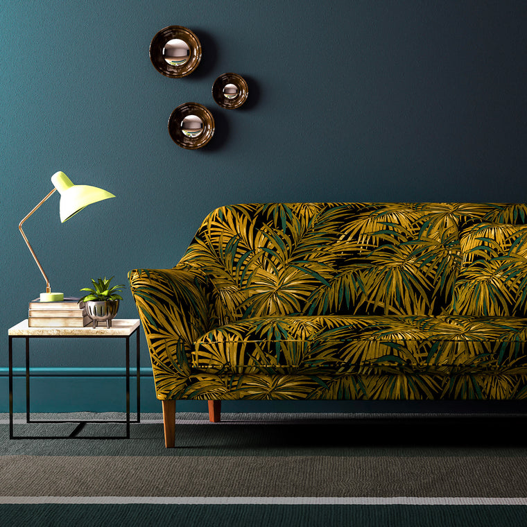 Velvet sofa upholstered in an gold and teal velvet upholstery fabric with palm design and stain resistant finish