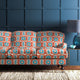 Velvet sofa upholstered in a orange and blue velvet upholstery fabric with abstract print and stain resistant finish
