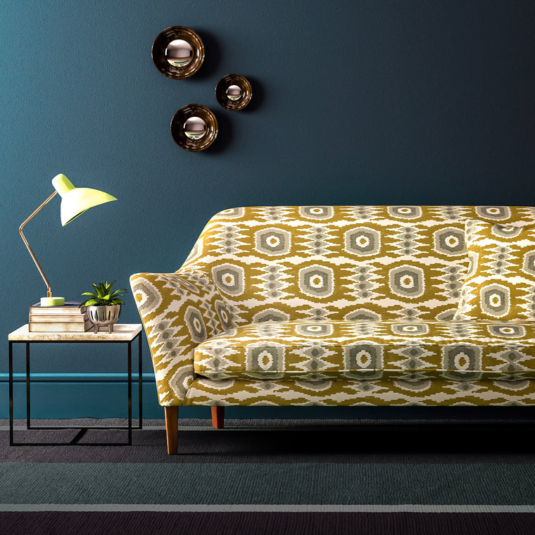 Sofa upholstered in a ochre velvet upholstery fabric with abstract print and stain resistant finish