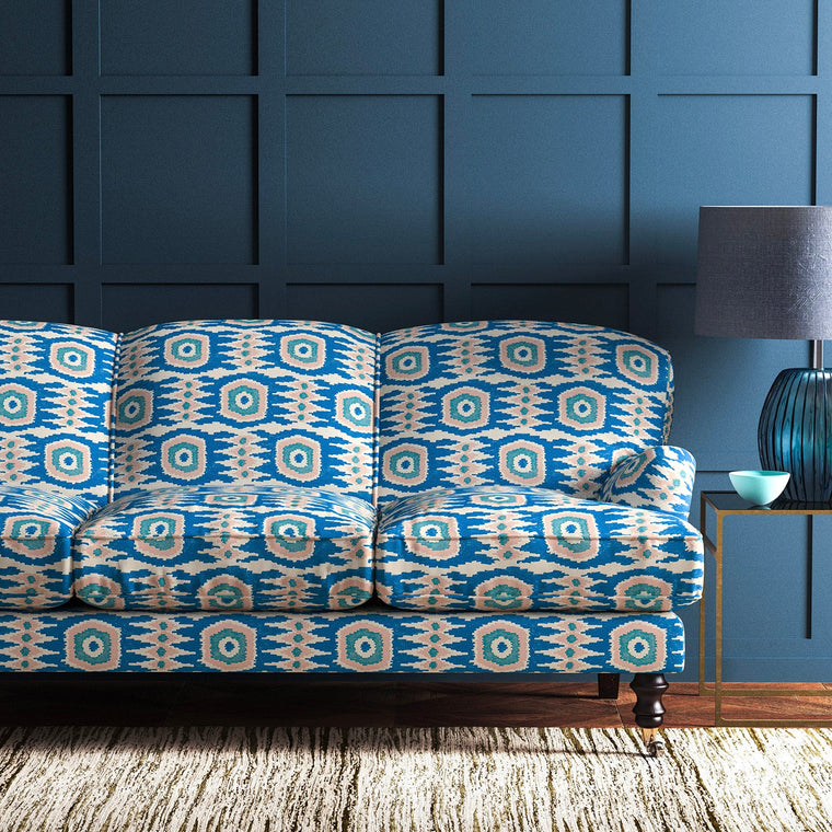 Sofa upholstered in a light pink and blue velvet upholstery fabric with abstract print and stain resistant finish