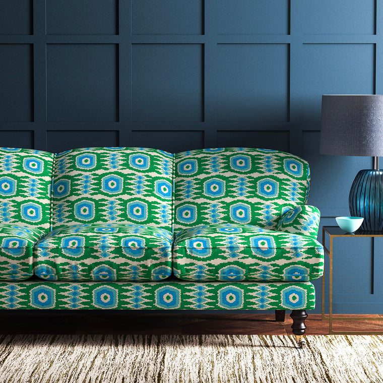 Velvet sofa upholstered in a green and blue velvet upholstery fabric with abstract print and stain resistant finish