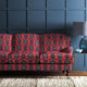 Velvet sofa upholstered in a red and blue velvet upholstery fabric with abstract print and stain resistant finish