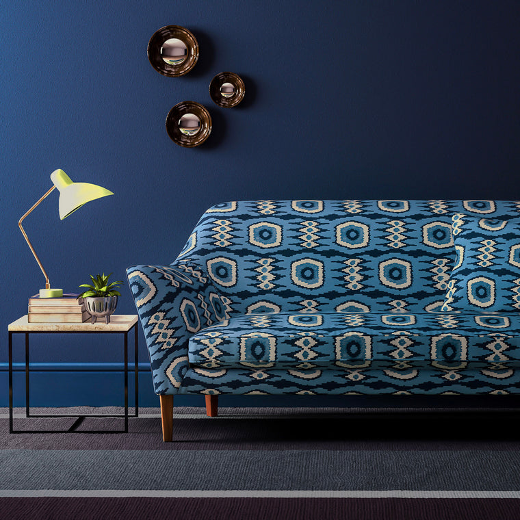 Sofa upholstered in a blue velvet upholstery fabric with abstract print and stain resistant finish