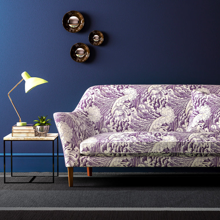 Velvet sofa upholstered in a purple and white velvet upholstery fabric with a wave design and stain resistant finish