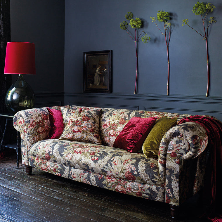 Sofa upholstered in a luxury dark blue and pink floral bouquet fabric