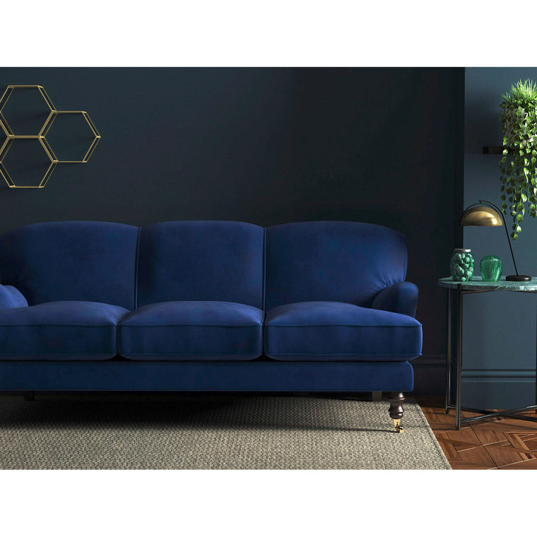 Sofa upholstered in a dark blue velvet fabric with a stain resistant finish