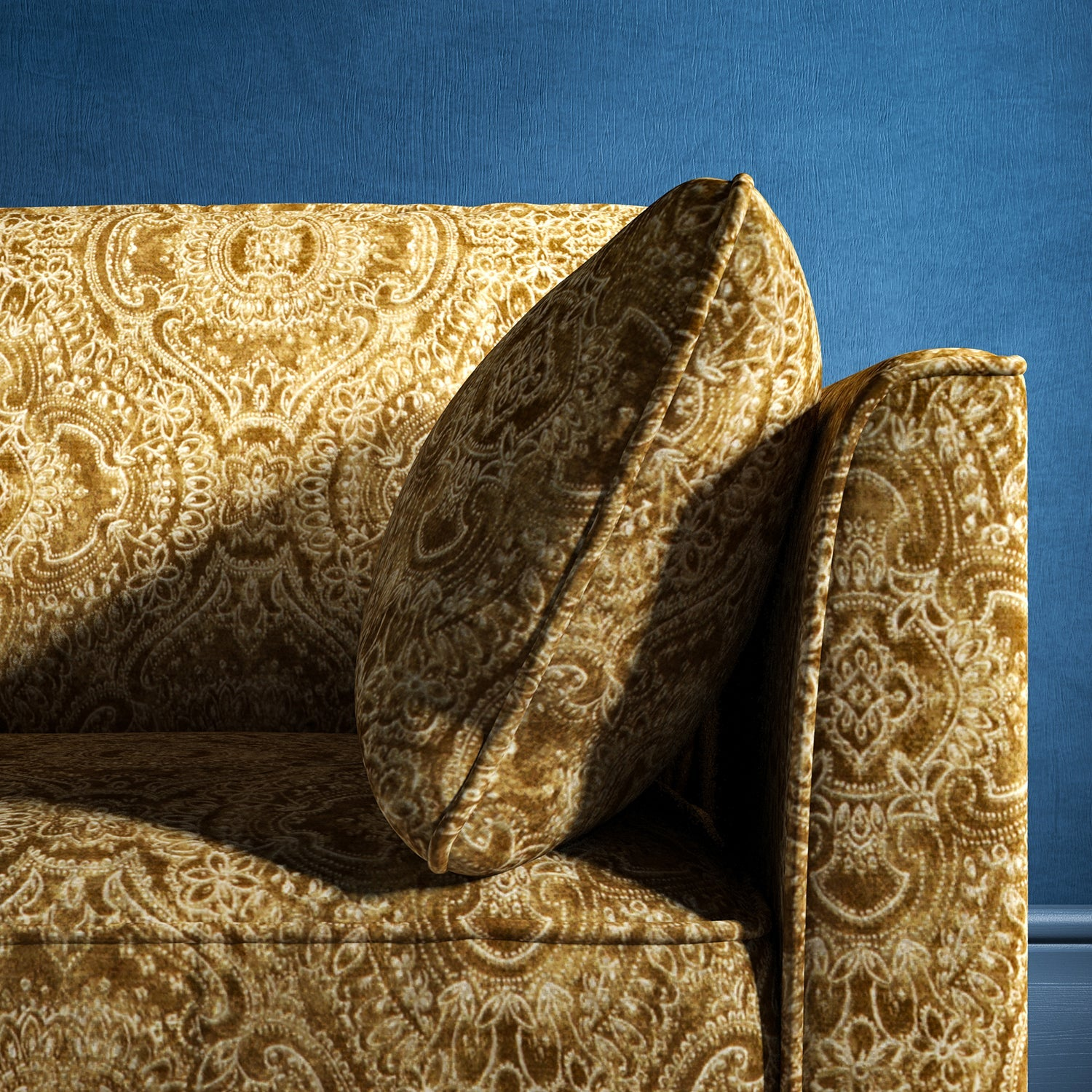 Sofa upholstered in a gold upholstery fabric with intricate jewel like design