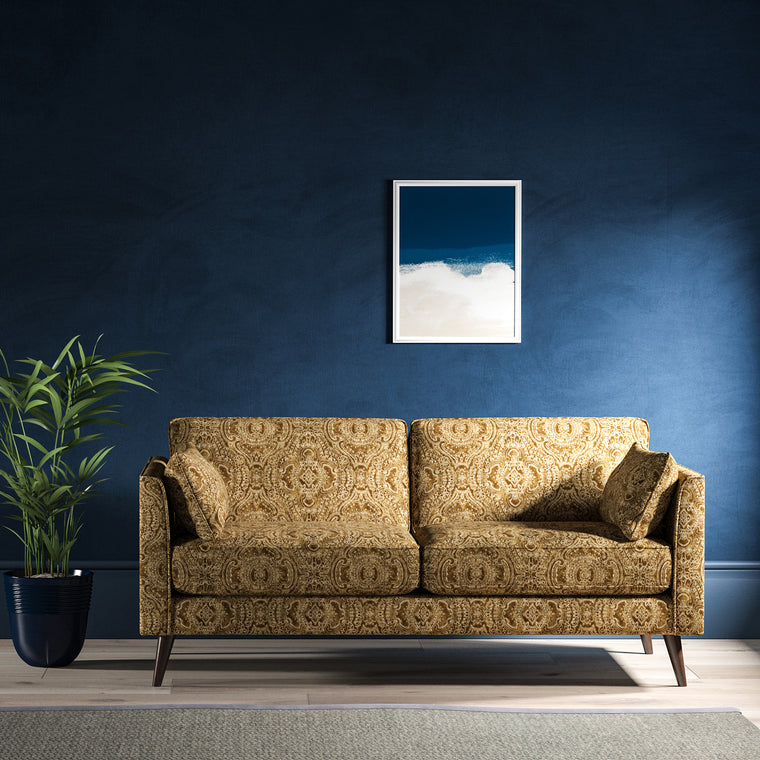Sofa upholstered in a gold velvet upholstery fabric with intricate jewel like design