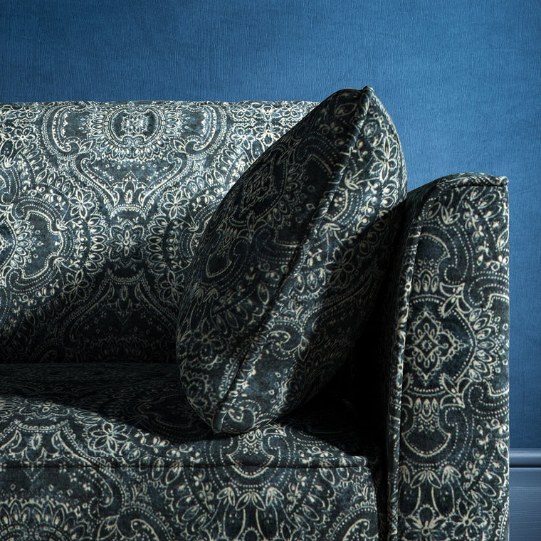 Sofa upholstered in a dark blue velvet upholstery fabric with intricate jewel like design