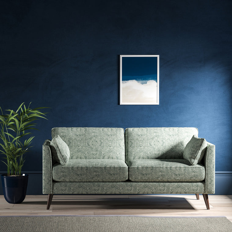 Sofa upholstered in a smokey blue upholstery fabric with intricate jewel like design