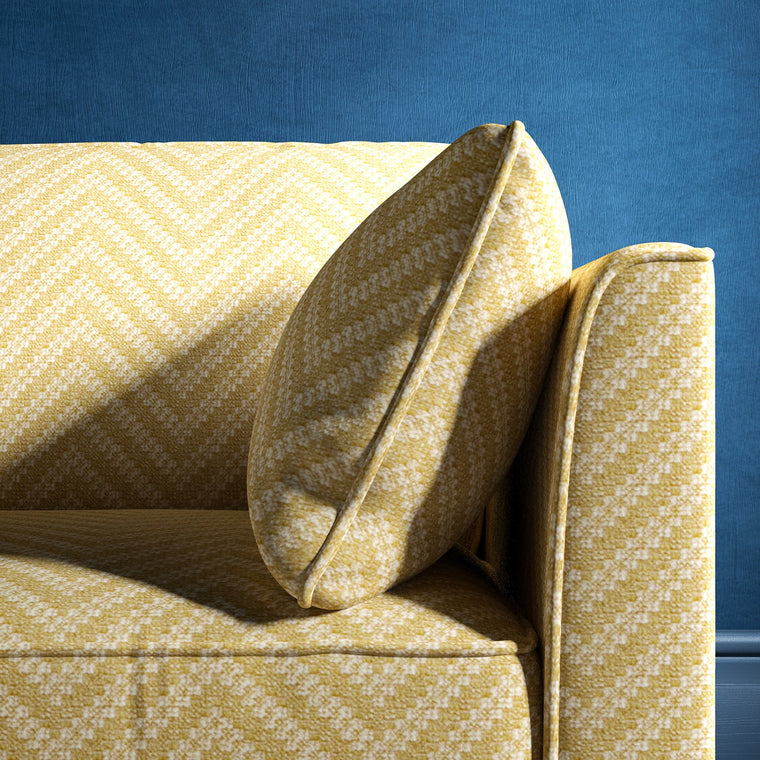 Sofa upholstered in a light yellow and neutral herringbone upholstery fabric