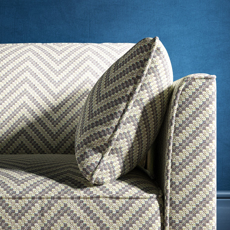 Sofa upholstered in a grey and neutral herringbone upholstery fabric