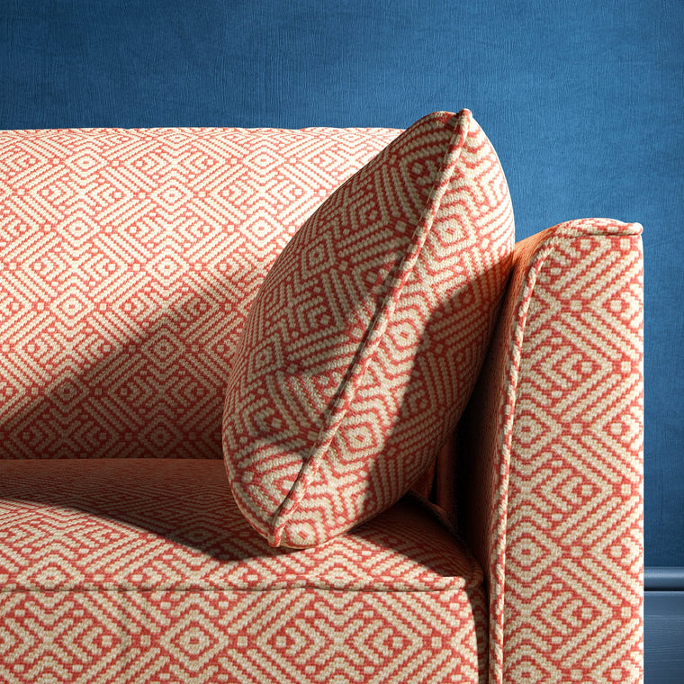 Sofa upholstered in a pink and neutral geometric weave upholstery fabric