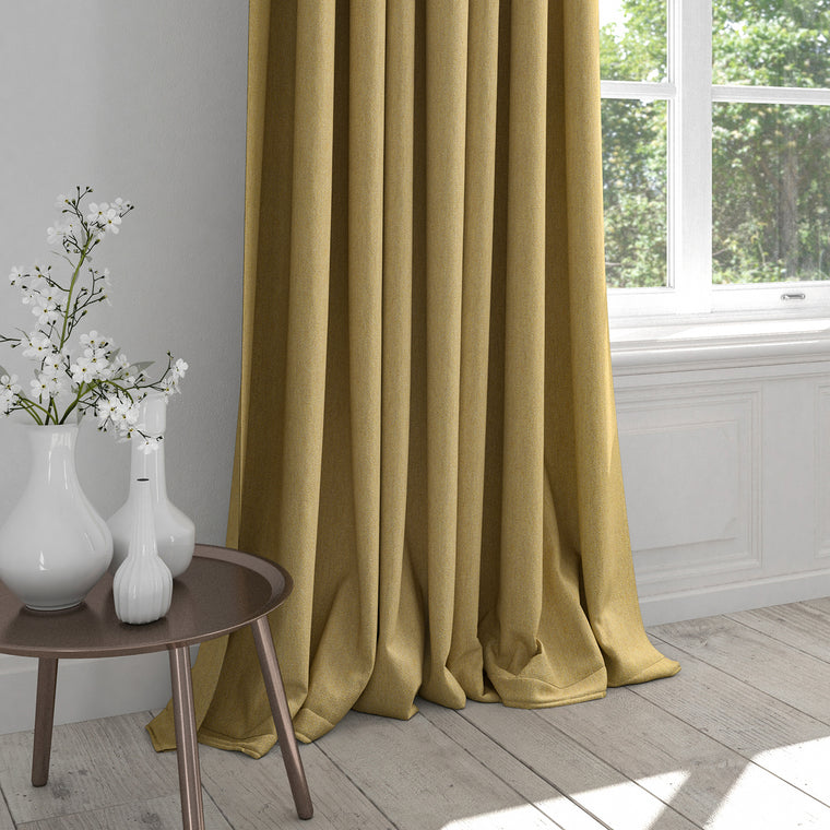 Curtain in a light yellow fabric with a light neutral woven geometric design