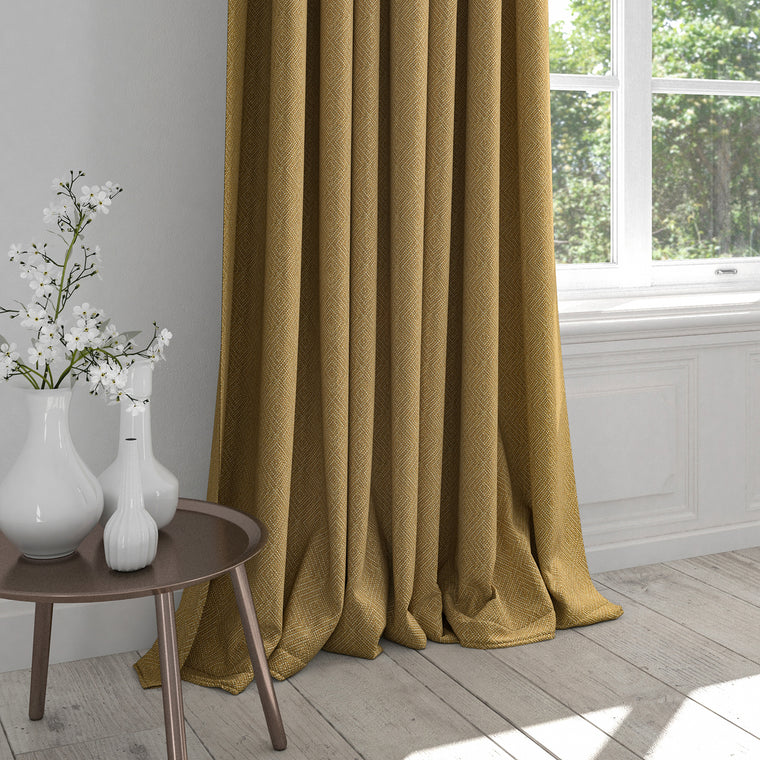 Curtain in a mustard yellow fabric with a light woven geometric design
